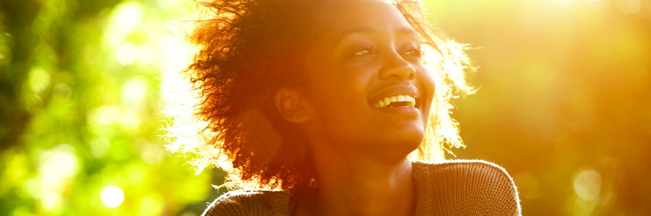 Close up portrait of a woman smiling with sunset
