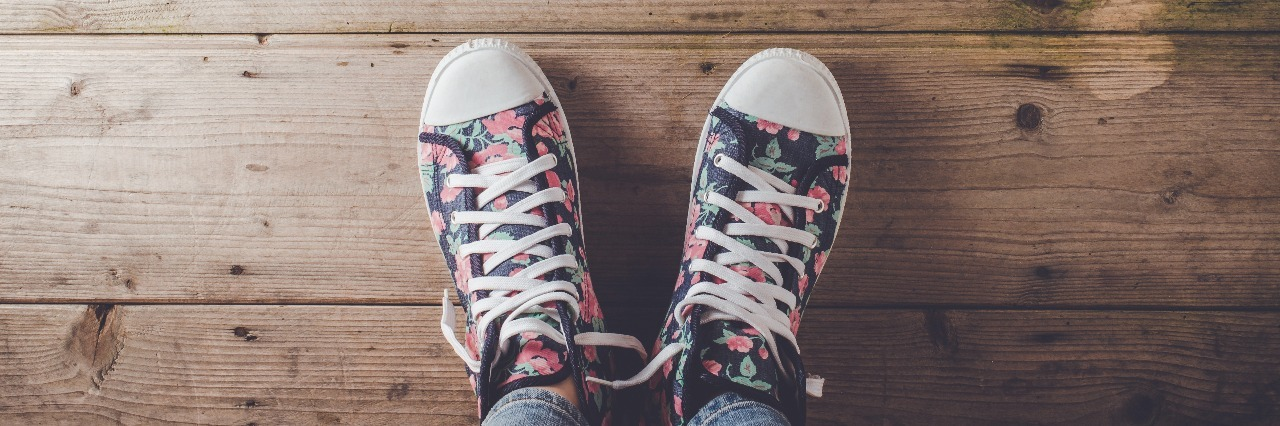 floral pattern sneakers standing on old wooden floor