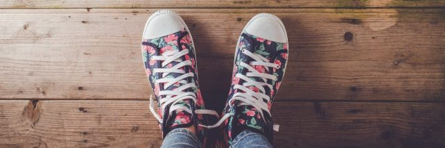 Female sneakers with floral pattern standing on an old wooden floor