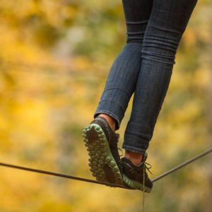 Girl walking along a tightrope in the trees.