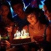 girl blowing out candles on a birthday cake surrounded by friends