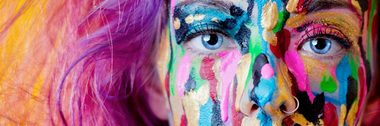 close up woman with purple hair covered in paint