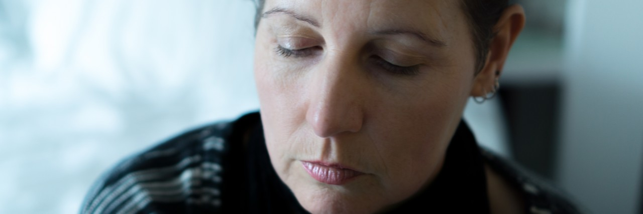 A middle aged woman looking pensive and sad