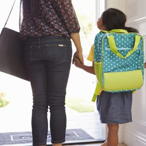 Mother and daughter holding hands, walking out door of home on the way to school