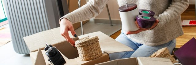 Woman packing and putting items into boxes at home