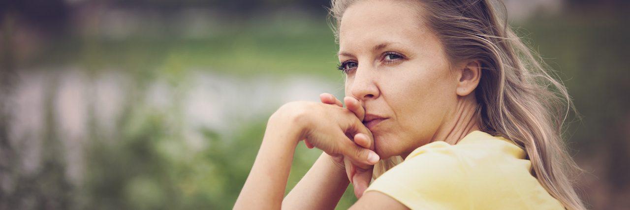 A woman sitting by a lake