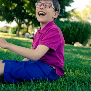 Happy boy with cerebral palsy sitting outside.