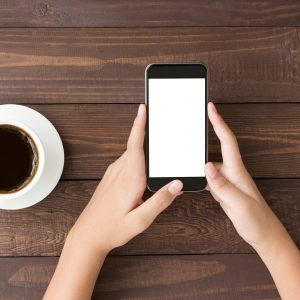 phone white screen in woman hand on table top view