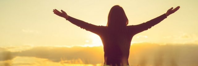 woman in field with sunset spreading arms wide feeling free