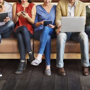 row of people sitting on bench looking at phones or laptops