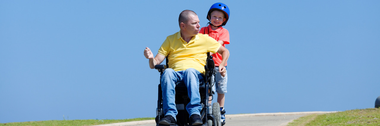 Father in a wheelchair playing with his son.