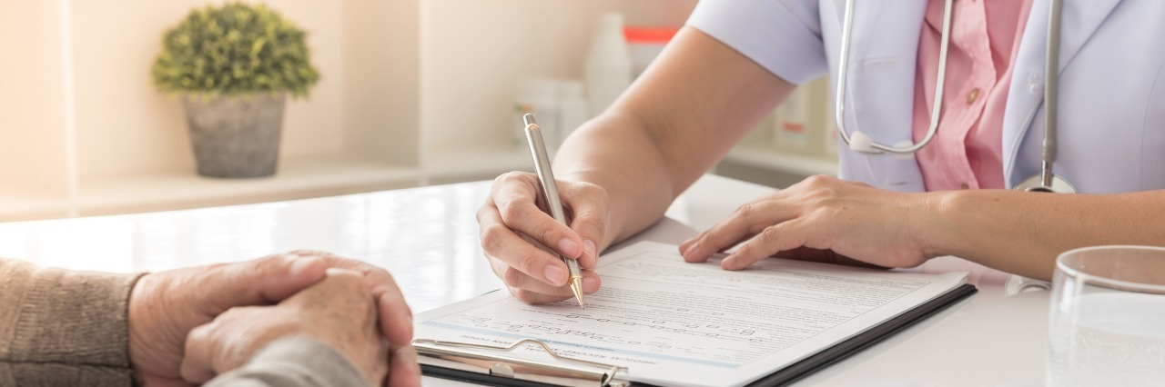 doctor writing notes while sitting at a table and talking with a patient