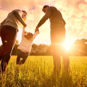 Happy family in the park at sunset.