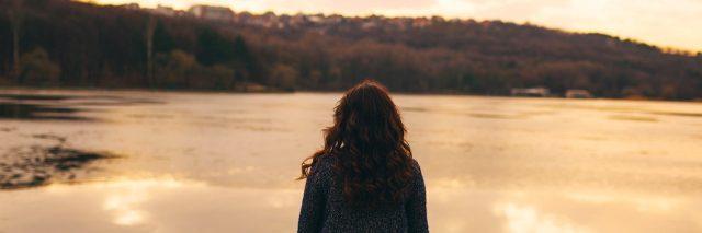 Woman wearing jacket, standing near lake at sunset