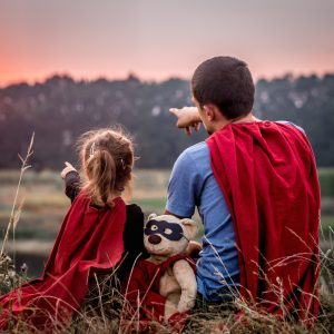 little girl with dad dressed in super heroes,
