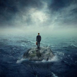 A man standing on a rock in the ocean