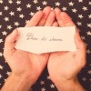 a piece of paper that says [dare to dream] on palms of someone's hands, with a star background