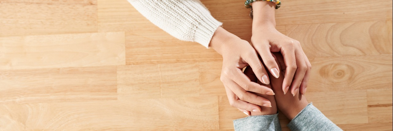 people holding hands across table compassion
