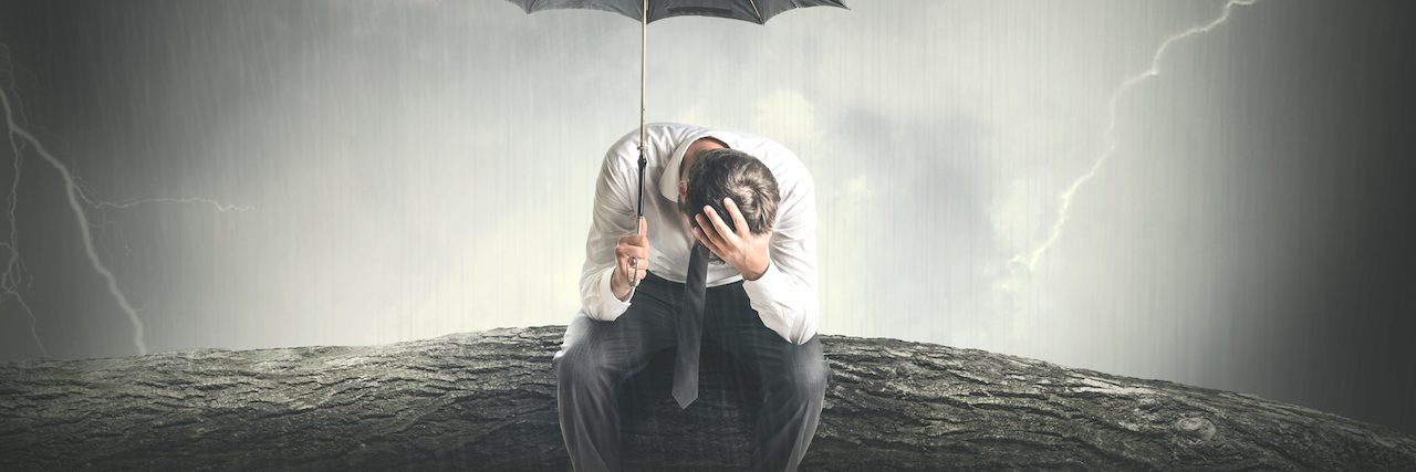 A man sitting on a branch in the rain, holding an umbrella