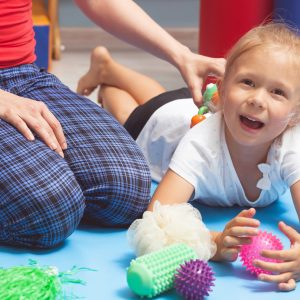 Physical therapist helping child play with colorful textured toys.