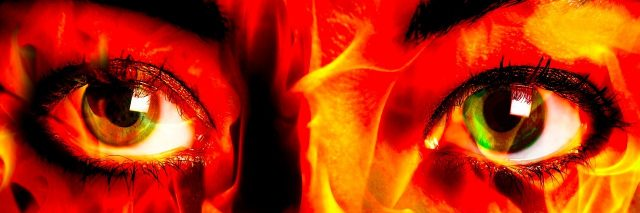 close up of woman's eyes with flame pattern over face