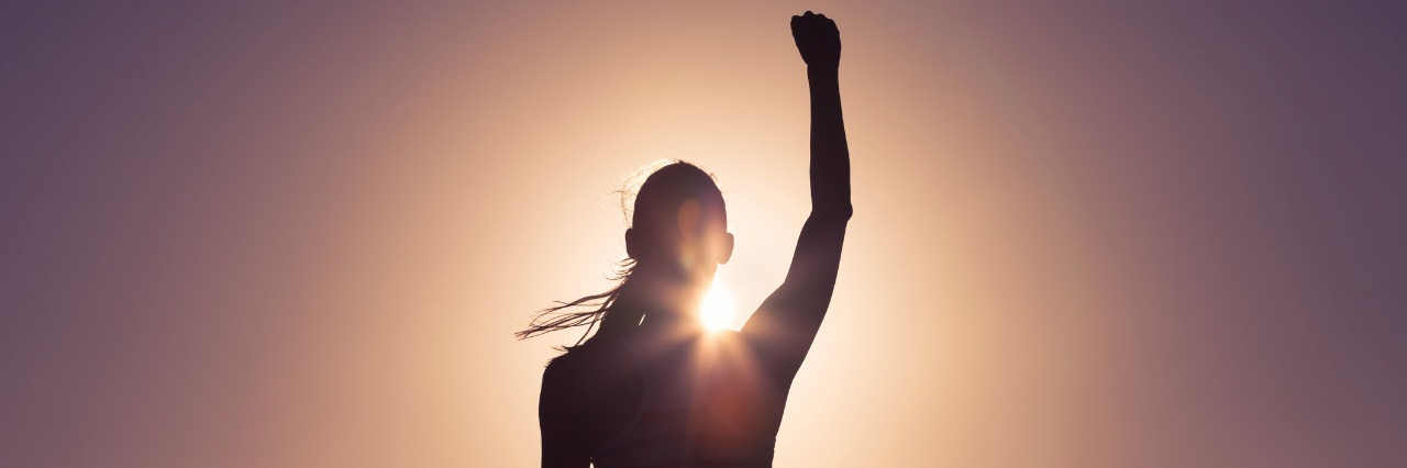 silhouette of a woman pumping her fist in the air