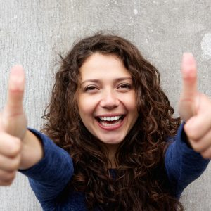 Portrait of smiling young woman giving thumbs ups with both hands against gray wall
