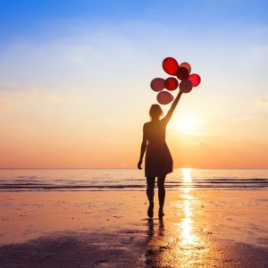 woman on beach at sunset holding balloons