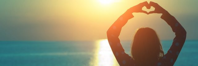 woman heart symbol hands in front of sunset over ocean