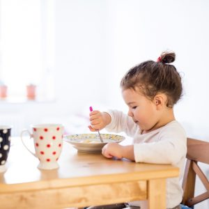 Girl sitting at table in kitchen, eating breakfast