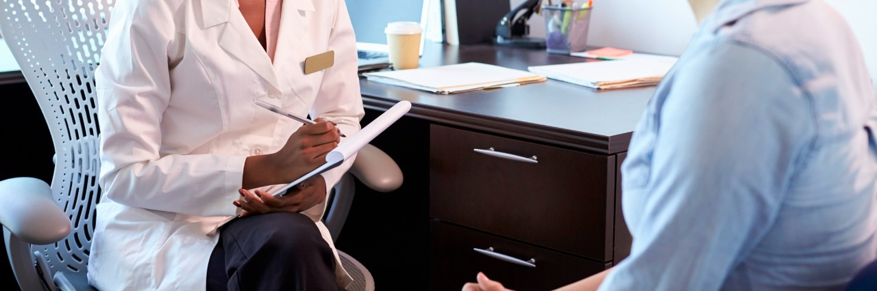 Doctor In Consultation With Female Patient In Office