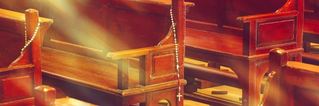 wooden church pews in church and rosary beads with sunlight