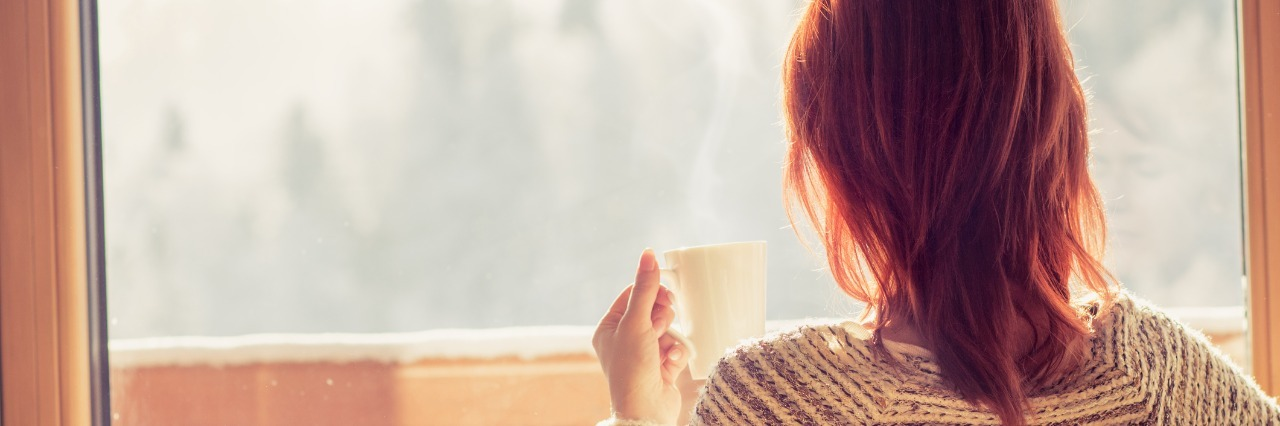 woman sitting in a chair and holding a mug of coffee while looking out the window