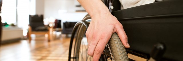 Woman in wheelchair at home in living room.