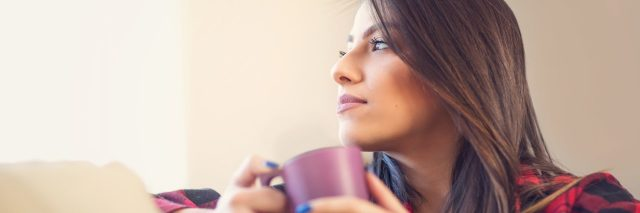 woman holding mug and sitting on her couch looking off into the distance