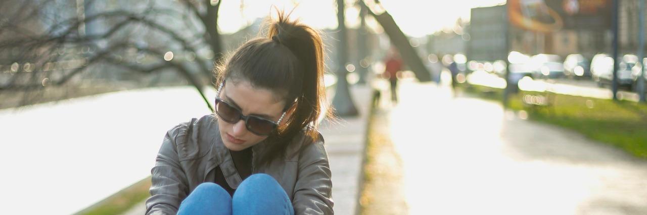 young woman sitting alone and sad, urban scene