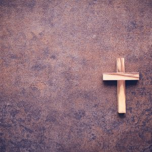 He is risen word and wooden cross on dark background