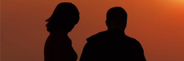 Silhouette of man and woman at sunset on beach