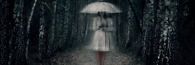 woman standing in woods holding umbrella