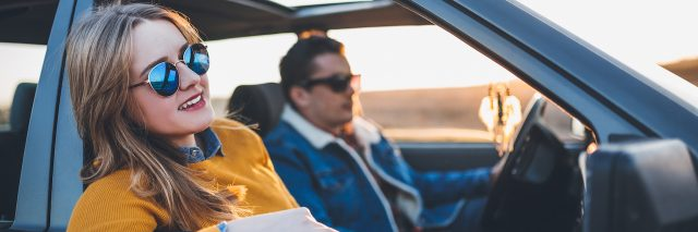 Young couple on a road trip, in car enjoying ride in sunset