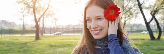 woman smiling outside in a park with a red flower in her hair