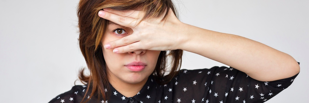 A woman covers her face with her hands