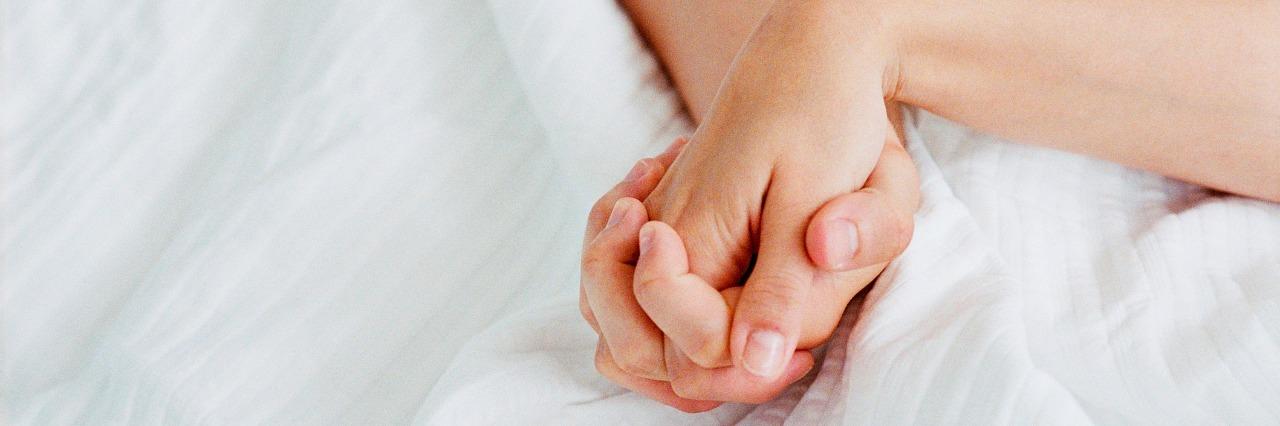 hands holding on white blanket
