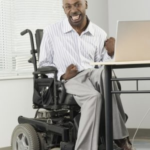 Businessman with cerebral palsy sitting in a wheelchair and working on a computer with his foot.