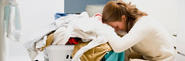 Exhausted woman sleeping by basket of laundry
