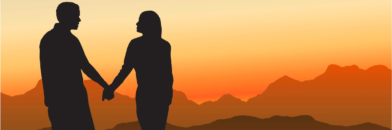Silhouette of couple holding hands in front of mountain landscape at sunset