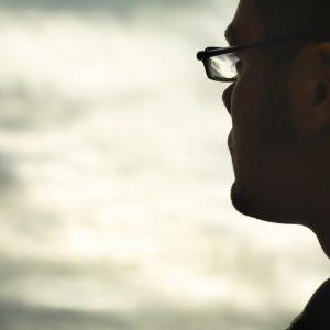 Profile of man wearing glasses, looking toward clouds in sky