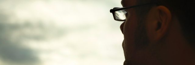 Profile of man wearing glasses, looking toward clouds in sky