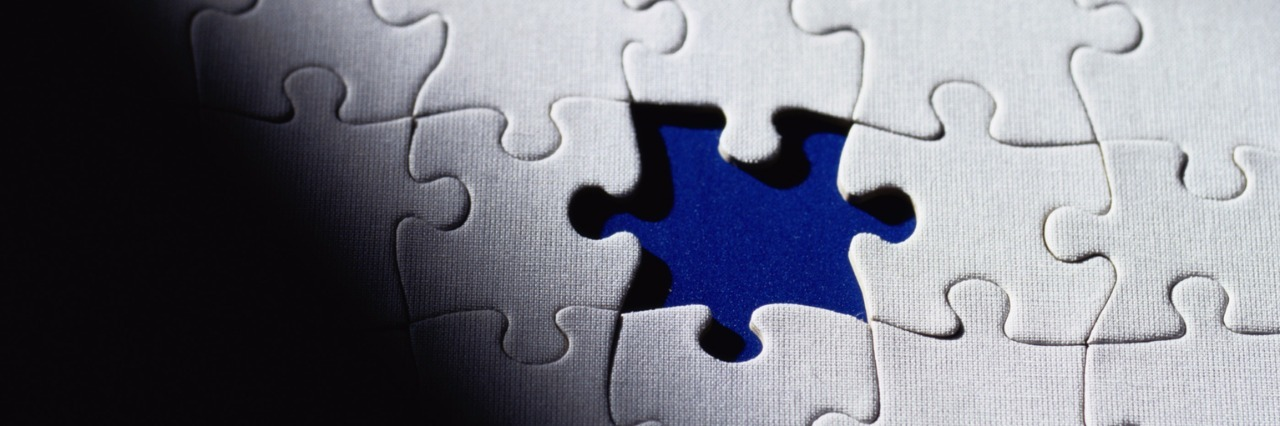 White puzzle pieces, with a blue background, framed by black shadow.