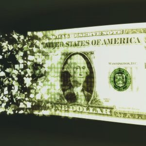 US dollar bill crumbling into pieces.